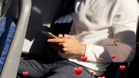 приложение : Digital composite of a man sitting on a bus while texting with digital hearts flying in the foreground Стоковые видеозаписи