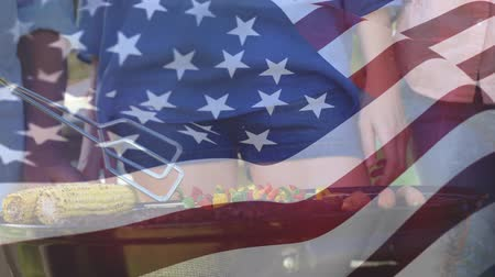 old glory : Digital composite of people grilling and an american flag waving in the foreground Stock Footage