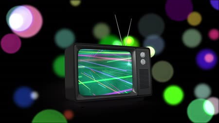 changing lights : Digital animation of a television with beams of light on its screen and a black background filled with bokeh lights