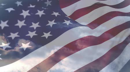 spangled : Digital composite of an American flag waving on a clear blue sky Stock Footage