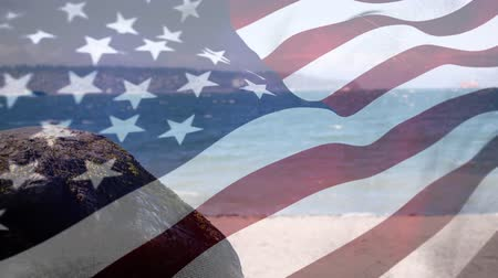 dc : Digital composite of a beach with an american flag waving in the foreground