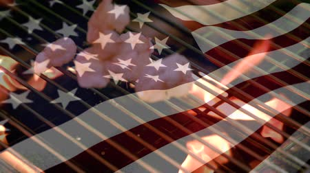 spangled : Digital composite of a grill with shrimps and an American flag waving in the foreground Stock Footage