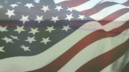 plain : Digital composite of a wide grass field with an American flag waving in the foreground