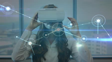 развлекать : Digital composite of a Caucasian woman taping in the air while wearing a virtual reality headset with connected lines and circles in the foreground