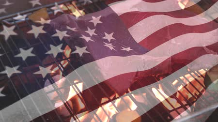 ábrázol : Digital composite of an American flag waving and grill on fire is seen on the background Stock mozgókép
