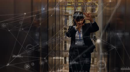 tendo : Digital composite of a business woman wearing a virtual reality headset in a hallway. Dots and lines connected are seen moving in the foreground Vídeos