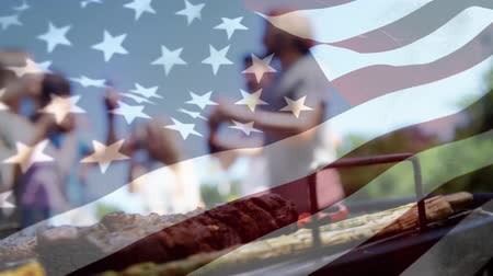 spangled : Digital composite of friends drinking beer while having a barbecue and an American flag waving in the foreground Stock Footage