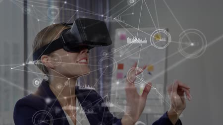 развлекать : Digital composite of a Caucasian businesswoman typing in the air while wearing a virtual reality headset with lines and graphs in the foreground