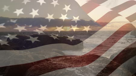영광 : Digital composite of waves splashing against a rocky shore at sunset with an American flag waving in the foreground