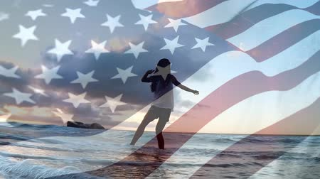 dc : Digital composite of a woman playing with waves on the beach with an American flag waving in the foreground