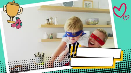герои : Close up of a mother carrying her son while wearing superhero costumes in the kitchen in a digital photo border effect Стоковые видеозаписи