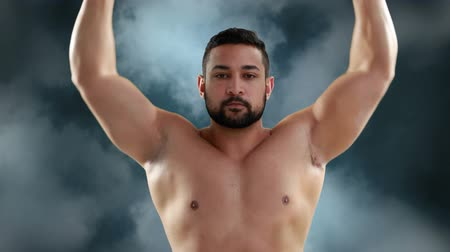 construção muscular : Digital composite of a Caucasian shirtless man lifting dumbbells in a foggy background