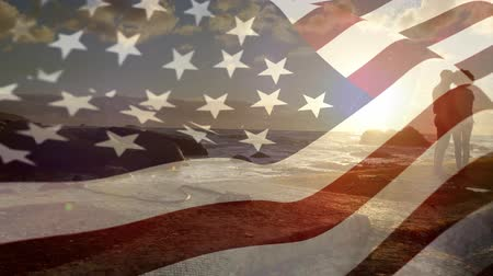 dc : Digital composite of an American flag waving against the wind with a couple on a beach Stock Footage
