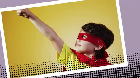 развлекать : Front view of a Caucasian boy wearing a superhero costume posing in a digital photo border effect