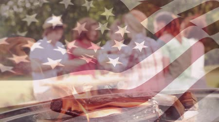 usa independence day : Digital composite of a group of friends having a barbecue with an american flag waving in the foreground Stock Footage