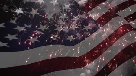 spangled : Digital composite of a fireworks display with an American flag waving in the foreground