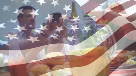spangled : Digital composite of a happy family with friends having a picnic with an American flag waving in the foreground