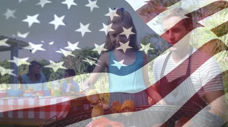 spangled : Digital composite of a Caucasian father teaching his daughter to grill while behind them is the mother with their son on the picnic table. American flag is waving in the foreground Stock Footage