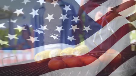 spangled : Digital composite of friends cooking on a grill with an American flag waving in the foreground Stock Footage
