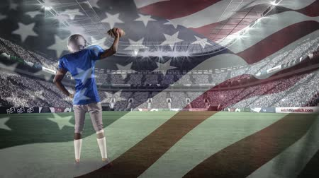 spangled : Digital composite of an African-american football player standing on the field while raising the ball with an American flag waving in the foreground Stock Footage