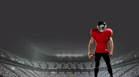 dobrar : Front view of an American football player holding the ball on the field Stock Footage