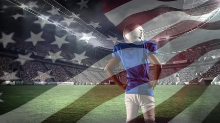 stadion : Digital composite of an African-american football player standing on the field with an American flag waving in the foreground
