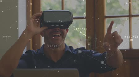 развлекать : Digital composite of a Caucasian man wearing a virtual reality headset having fun with connected dots and lines in the foreground