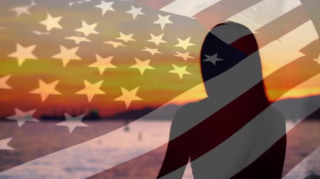 フォアグラウンド : Digital composite of a woman staring at the ocean at sunset with an American flag waving in the foreground 動画素材