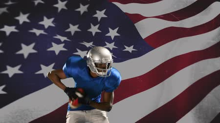dc : Front view of an African-american football player throwing the ball with an American flag waving in the foreground