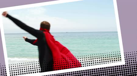 heroes : Digital animation of a Caucasian man wearing a superhero costume on the beach with a photo border effect. Man is running around pretending to fly Stock Footage
