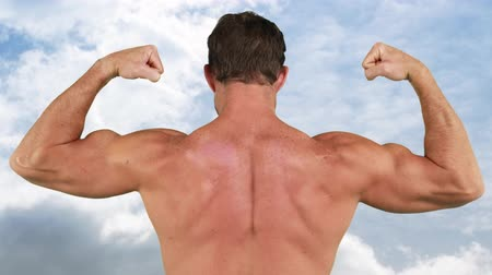 construção muscular : Rear view of a male bodybuilder flexing his back muscles with a sky background
