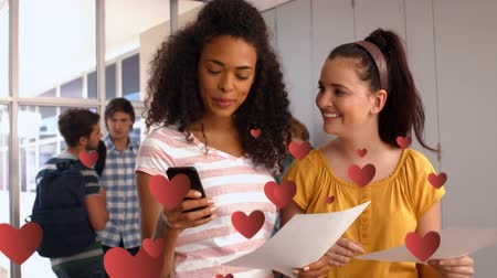 fondness : Digital composite of two girls showing signs of infatuation while reading text messages at a school hallway. Digital hearts are slowly flying in the foreground. Two guys are seen talking in the background