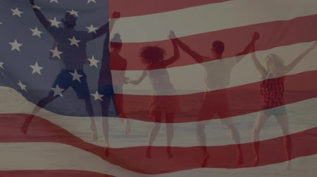 spangled : Digital composite of a group of people holding hands while jumping on the beach and an American flag waving in the foreground