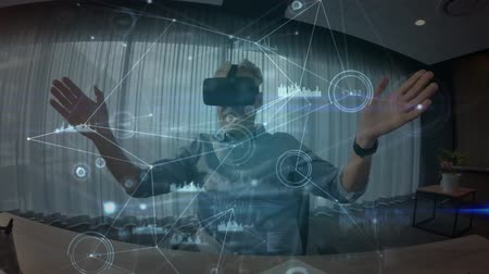 развлекать : Digital composite of a Caucasian man wearing a virtual reality headset while swiping his hands in the air with connected lines and graphs in the foreground