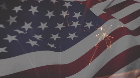 spangled : Digital composite of an American flag waving and sparklers in the foreground