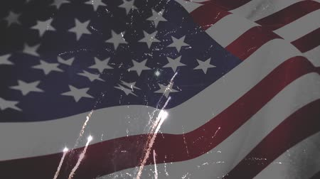 spangled : Digital composite of fireworks and an American flag waving in the foreground Stock Footage
