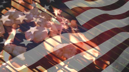 spangled : Digital composite of shrimps grilling and an American flag waiving in the foreground Stock Footage