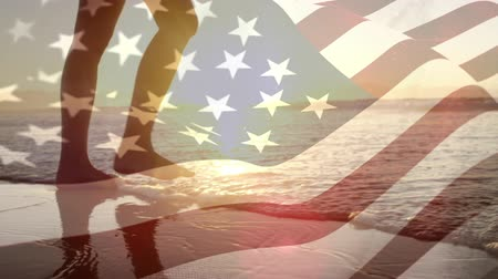 old glory : Digital composite of a woman walking by the beach at sundown and an American flag waving against the wind Stock Footage