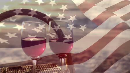 dc : Digital composite of two glasses of wine on the sand near the beach with an American flag waving in the foreground Stock Footage