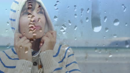 úmido : Digital composite of a Caucasian woman near the beach wearing a hoodie warming up with a glass filled with water droplets in the foreground