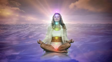 размышлять : Digital animation of a woman meditating on digital water with bright shining lights behind her