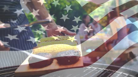 spangled : Digital composite of a man grilling corn and meat with an American flag waving in the foreground. Behind him are his friends mingling at a picnic table