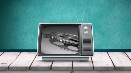changing channel : Digital animation of a television on a wooden table and a green background with a film roll on its screen