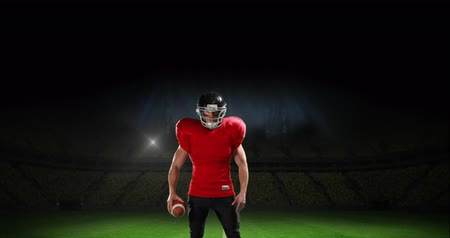 pólos : Front view of an American-football athlete hyping p for a game. Behind him is a stadium filled with people and flashing lights 4k
