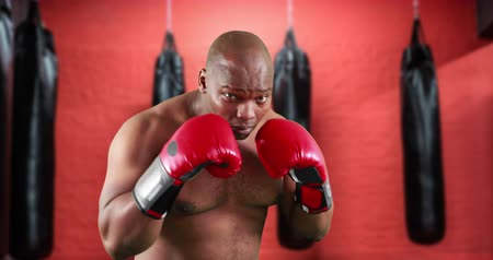 хмурый : Front view of an African-american man shadow boxing in the gym. Behind him are punching bags 4k