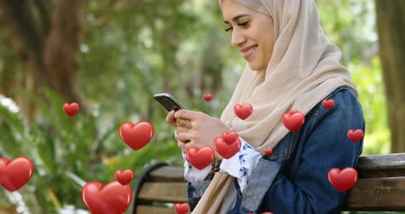 příloha : Digital composite of a Muslim woman wearing a hijab, sitting on a park bench smiling while texting and digital hearts flying in the foreground 4k
