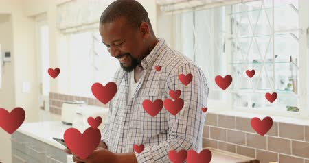 příloha : Digital animation of an African-american man texting and smiling in kitchen. Floating hearts are seen in the foreground 4k
