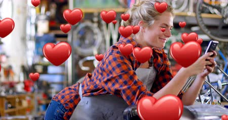 příloha : Digital composite of a Caucasian female bicycle mechanic leaning on a table smiling while texting and digital hearts flying in the foreground 4k