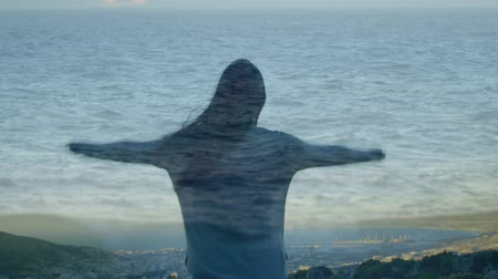 abandonment : Digital composite of a woman standing on top of a mountain overlooking the sea while raising her hands with an image of ocean water in the foreground