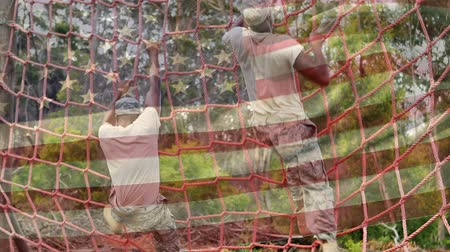 dobrar : Digital composite of two American soldiers climbing a cargo net with an American flag waving in the foreground Stock Footage